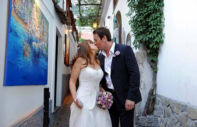Romantic kiss of a newlywed couple in Positano