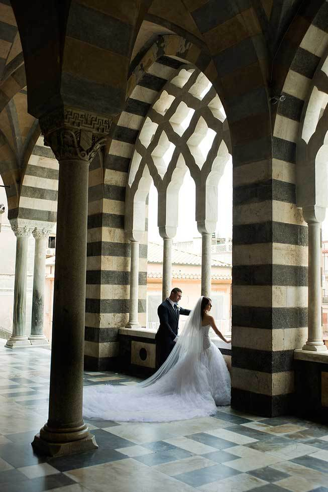 Bride and groom under the arches of the Amalfi Duomo