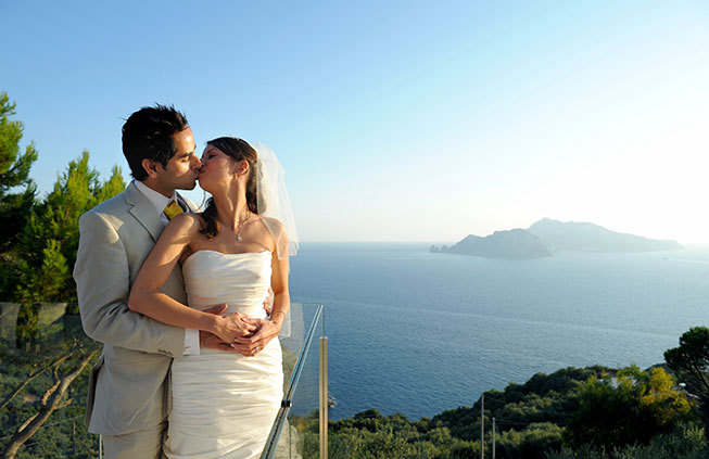 Newlyweds kissing on a terrace with seaview in Sorrento