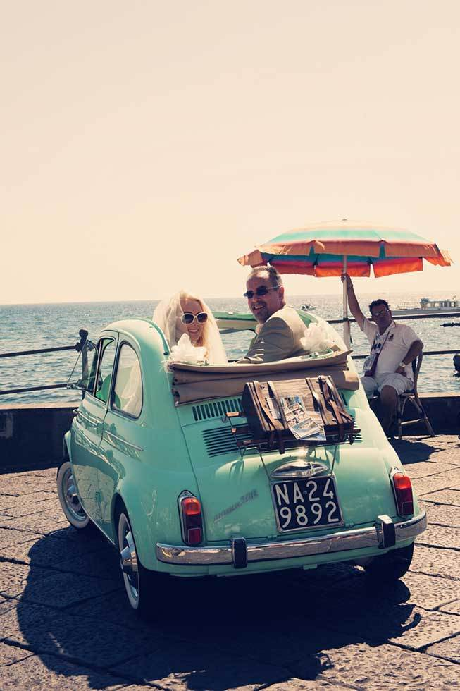 Bridal couple having fun on a vintage car in Atrani
