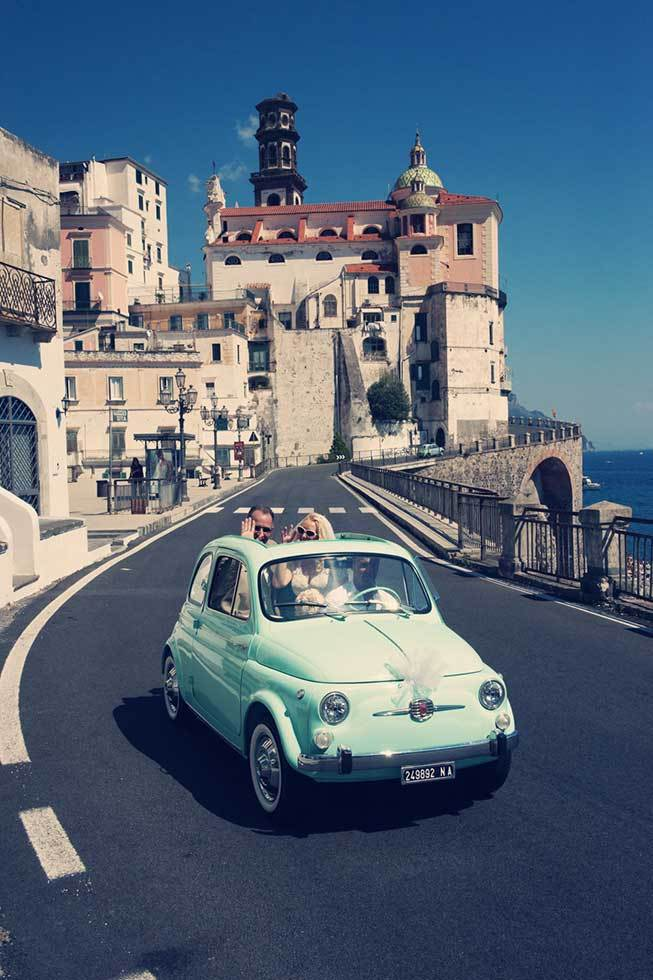 Bridal couple travelling on a vintage car in Atrani