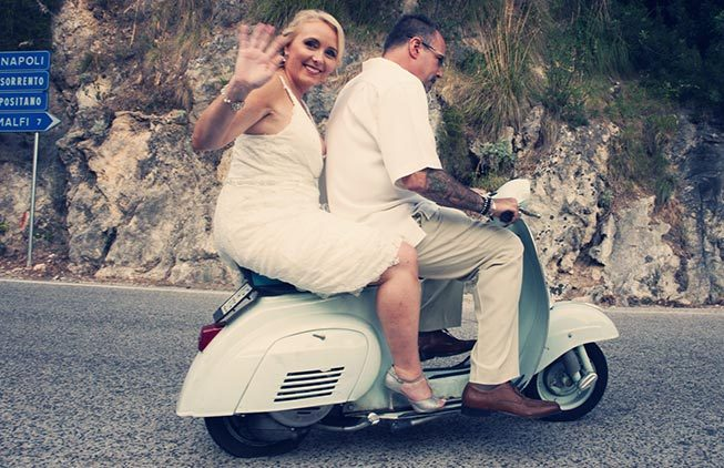 Bridal couple on a vintage Vespa scooter on the Amalfi Coast